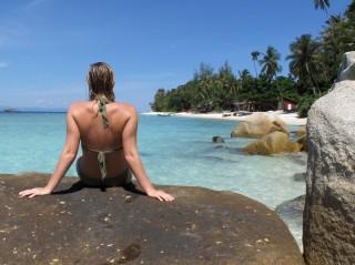Eine Kundin sitzt erholt am Strand