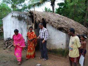 Einheimische vor einer Dorfhiütte