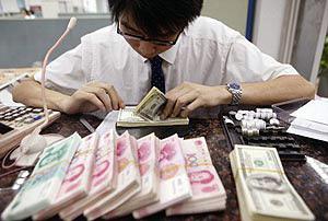 Ein Bankmitarbeiter hat die malaiische Währung vor sich liegen: Ringgit