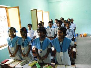 Schülerinnen in Uniform stehen im Klassenzimmer