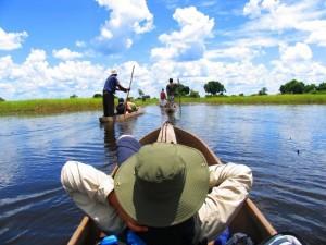 Botswana - Okavango Delta - Reisende unterwegs mit dem Mokoro durchs Okavango Delta - Rundreise Namibia Botswana