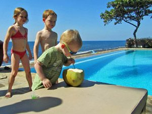 Kinder am Pool trinken eine Kokosnuss