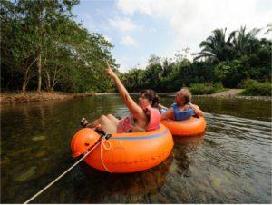 Reisende im Schwimmreifen auf dem Macal River
