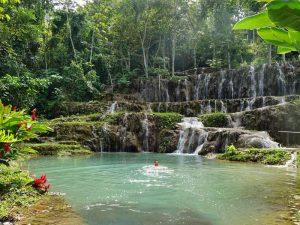 Auf dem Familienurlaub mit Teenagern an einem Wasserfall schwimmen