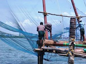 Arbeiter mit traditionellen Fischernetzen in Cochin