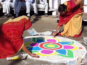 Einheimische Frauen bemalen die Straße in Deogarh