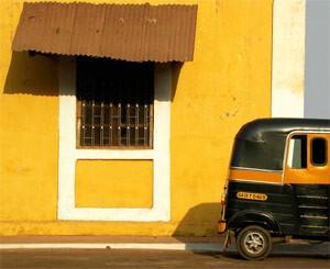 Rikscha vor gelbem Haus