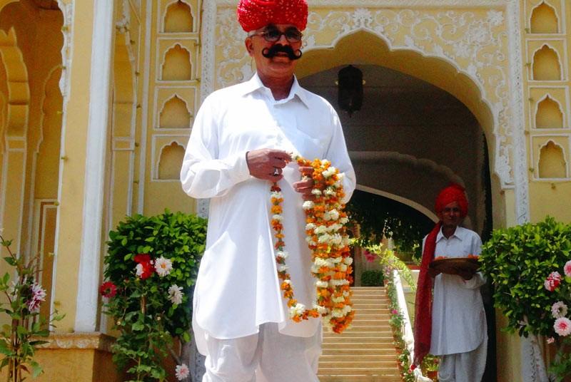 Kajasthan Rundreise: Ein Einheimischer empfängt sie mit einer Blumenkette am Samode Palast
