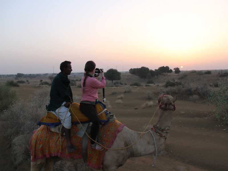 Sonnenaufgang auf dem Kamel in der Wüste in Jaisalmer auf einer Rundreise durch Indien