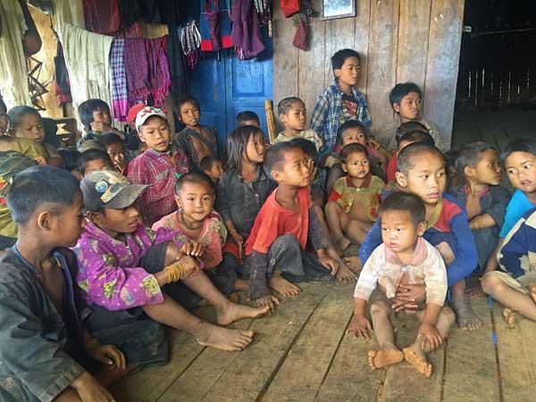 Kinder und Dorfbewohner in einem Akha Dorf
