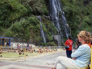Schwimmen in den Thermalquellen von Baños mit Blick auf die Wasserfälle