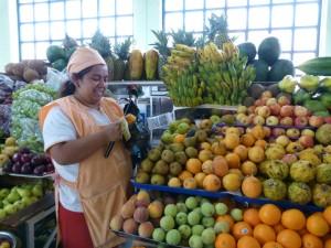 Marktfrau bereitet Obst zum Probieren vor