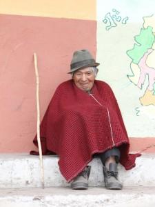 Alter Mann im Poncho sitzt vor Hauswand