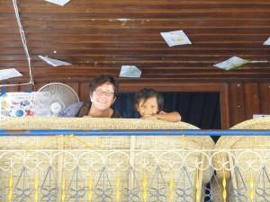 Kind und Erwachsener lachen vom Balkon des Kinderheimes herunter