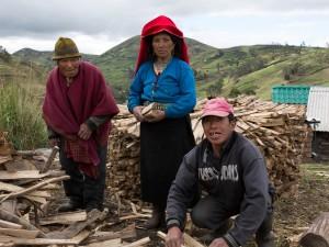 Drei Einheimische bei Holzarbeiten vor Bergkulisse