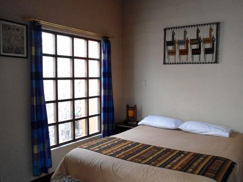 Doppelbett in einem einfachen Hotelzimmer in Quito