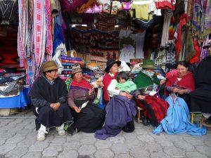 Hochlandsindios auf einem andinen Markt vor einem Verkaufsstand in Ecuador