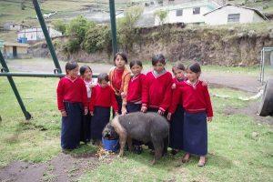 Kinder in Schuluniform mit Schwein bei der Schule