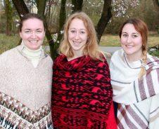 Drei Frauen mit Ponchos vor Kirschbaum