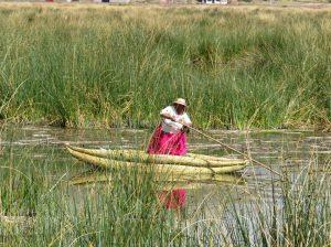 Frau im Schilfboot auf einem See