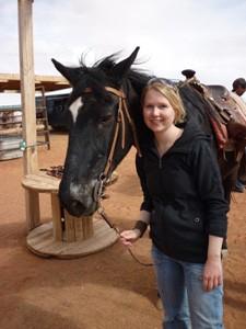 Ein Pferd posiert mit einer Reisenden im Monument Valley