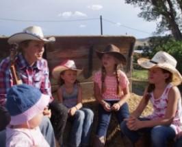 Frau mit Gitarre und Kinder sitzen im Kreis