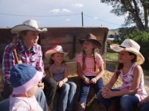 Frau mit Gitarre und Kinder sitzen im Kreis auf der Cowboy Ranch