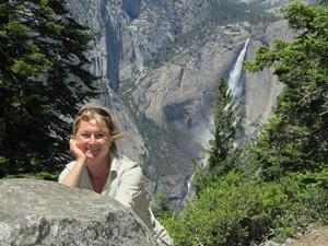 Eine Reisende posiert vor einem hohen Wasserfall im Yosemite