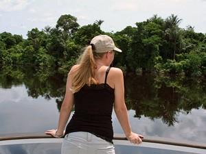 Frau blickt vom Schiff auf den Dschungel