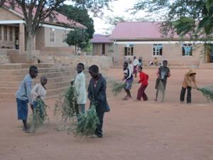 Kinder fegen den Dorfplatz