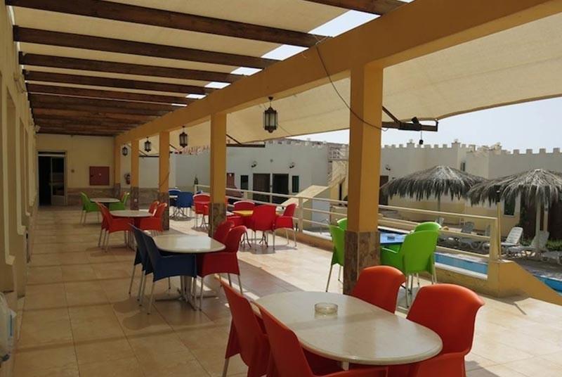 Terrasse mit Tischgruppen - Swimmingpool im Hintergrund