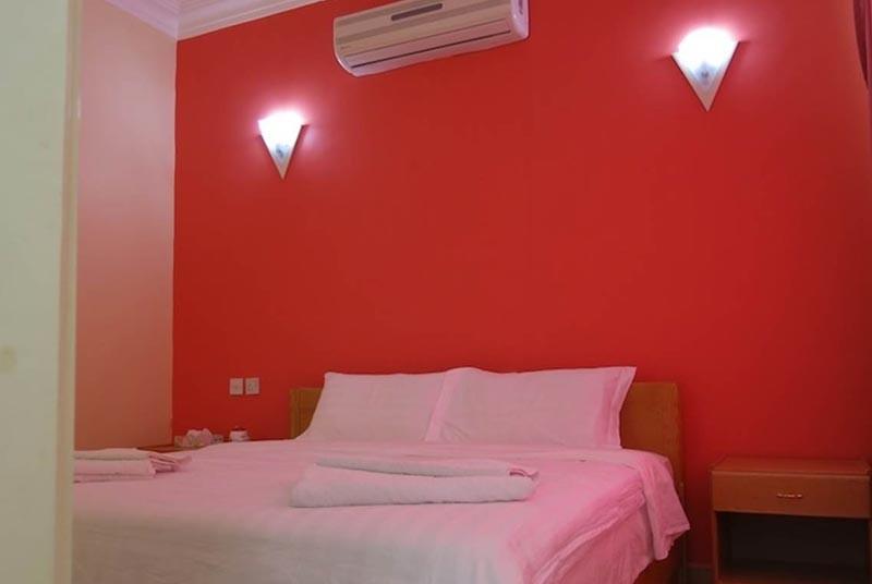 Zimmer mit Bett, Tisch und Klimaanlage