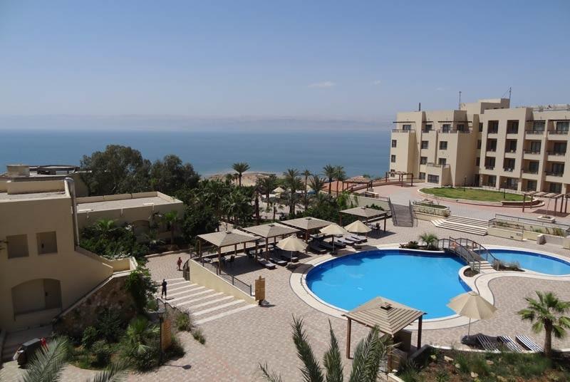 Rundreise Jordanien Blick auf die gepflegte Außenanlage des Hotels mit Swimmingpool und Palmen