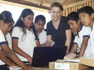 Frau überreicht Laptop an Schüler