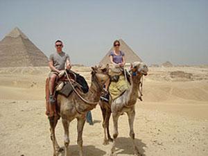 Touristen auf Kamele vor den Pyramiden in Ägypten