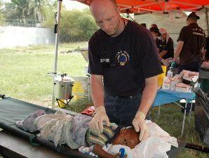 Mann vor einer Trage mit verletztem Kind