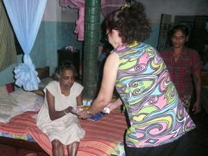 Frau überreicht Altenheim-Bewohnerin Essen