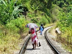 Einheimische spazieren auf den Gleisen bei Ella