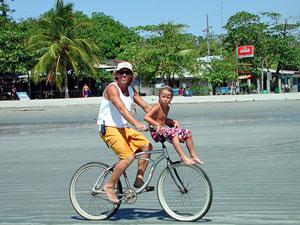 Ticos mit dem Fahrrad am Strand von Samara