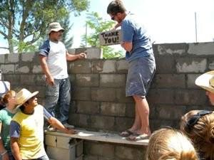 Mann mauert DANKE-Stein in Wand ein