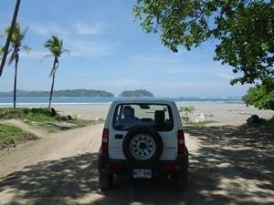 Blick auf den Mietwagen und den Strand im Hintergrund
