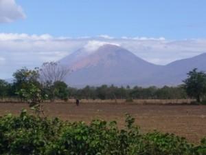 Vulkan hinter Feldern bei blauem Himmel