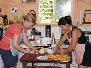 Gastgeberin und Reisende bereiten in Juanilama gemeinsam Essen zu