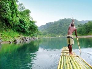 Einheimischer steht auf seinem Floß und paddelt auf dem Rio Grande