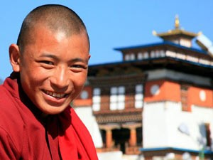 Lachender Mönch vor einem Tempel in Bhutan - Bhutan in Kürze