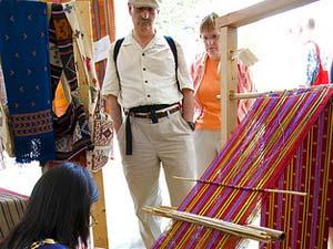 Touristen schauen Weberin bei ihrem Handwerk zu.