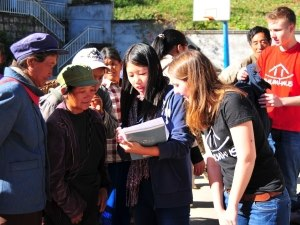 Helferin erklärt Einheimischen Ablauf der Kleiderverteilung