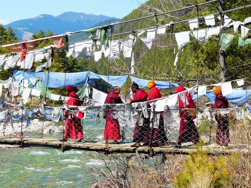 Mönche überqueren eine Hängebrücke bei Jakar
