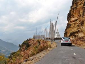 Stupa und weiße Gebetsfahnen entlang der Straßen Bhutans