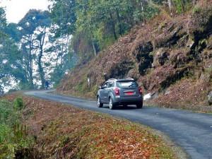 Auto auf schmaler kurviger Straße in Bhutan